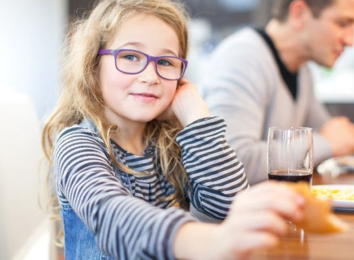girl wearigng glasses looks at camera as she enjoys a meal with the family