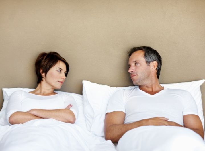 unhappy couple in bed looking at each other